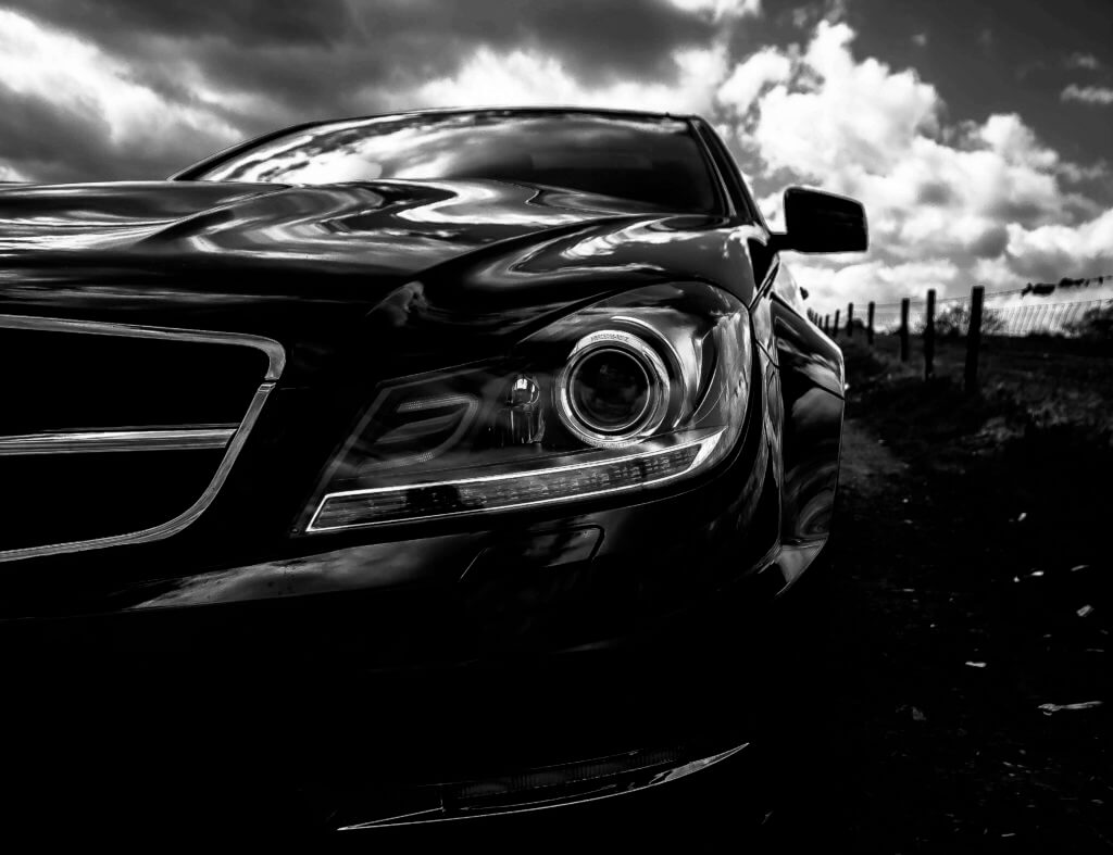 Black and White image of front of car with clouds in the background